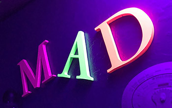 The letters MAD in neon colors from a mad science party room