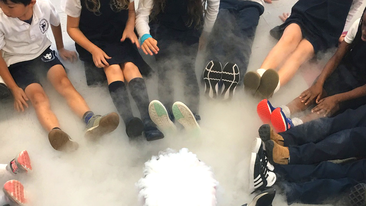 Kids sitting in a circle with legsd straigh out surrounding dry ice and smoke cause from the dry ice.