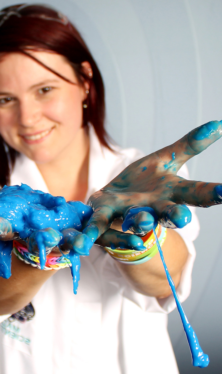 A mad scientist with blue slime in her hands